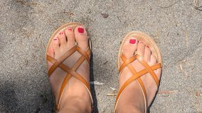 Chipped nail polish on toes in sandals on the beach. Feet with hipped red nail polish on toes in leather sandals on the beach stock photos