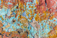 Chipped peeling paint on old wall. Close up of chipped peeling colorful paint on old wall Stock Photo
