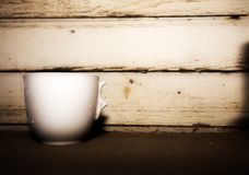 Chipped vintage white coffee cup. An old abandoned chipped white coffee cup on a dusty wood shelf Stock Photos