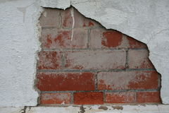 Chipped Wall. A cracked brick wall with old spackling and flaking paint Royalty Free Stock Photo