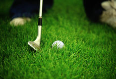 Chipping golf ball on to the green stock images