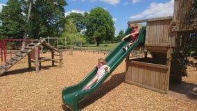 Chippings de madera y niños que deslizan abajo una diapositiva verde Fotografía de archivo