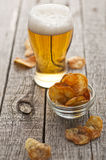 Chips. Homemade crispy potato chips with black salt and cold beer Royalty Free Stock Image