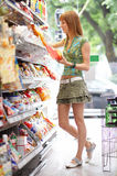 Chips. Red haired beauty while shopping all brandmarks removed Royalty Free Stock Photo