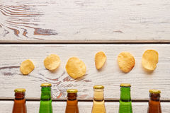 Chips above beer bottlenecks, wooden background. stock photo