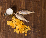 Chips, beer and two fishes. Dried fishes with frothy beer next to  diffuse crunchy chips on the table Royalty Free Stock Photos