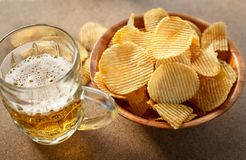 Chips and beer on a wooden table stock photos