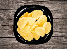 Chips on a black plate Stock Photography