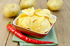 Chips in a bowl with hot peppers and potatoes on board Royalty Free Stock Photos