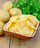 Chips in a bowl with a potato on the board. Potato chips in a clay bowl, fresh potatoes, parsley on a wooden boards background Royalty Free Stock Images