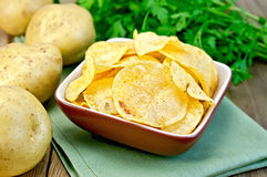 Chips in a bowl with a potato on the board and napkin. Potato chips in a clay bowl on a napkin, fresh potatoes, parsley on a wooden boards background Stock Photos