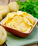 Chips in bowl with potato on napkin and board. Potato chips in a clay bowl on a napkin, fresh potatoes, parsley on a wooden boards background Royalty Free Stock Photos