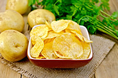 Chips in bowl with potatoes on sacking and board Stock Photo