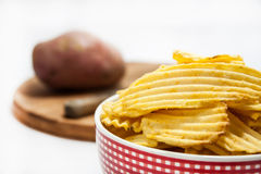 Chips in the bowl with raw potato in the background Stock Photos