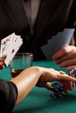 Chips and cards. A closeup of a women golding blue casino chips and cards Royalty Free Stock Photography