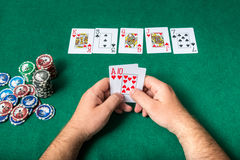 Chips and cards for poker in hand on green table Stock Image