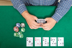 Chips and cards for poker in hand on green table, top view Royalty Free Stock Photos