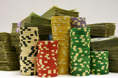 Chips and Cash. Several colorful stacks of poker chips in front of large stacks of U.S. currency Royalty Free Stock Image