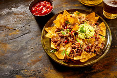 Chips with cheese, meat, guacamole and salsa Stock Photos