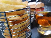 Chips chipbasket metalbasket plate cutlery whisky Royalty Free Stock Images