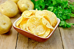 Chips in clay bowl with potatoes on board. Potato chips in a clay bowl, fresh potatoes, parsley on a wooden boards background Stock Images