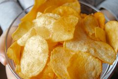 Chips close-up, in a glass container. A child holds a bunch of yellow chips royalty free stock photo
