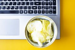 Snacking with junk food at the laptop. Chips and cola are near the laptop. Junk food. Snack in the break between work Stock Photo