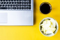 Snacking with junk food at the laptop. Chips and cola are near the laptop. Junk food. Snack in the break between work Royalty Free Stock Photo