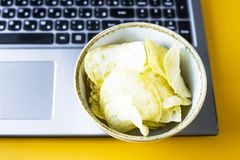 Snacking with junk food at the laptop. Chips and cola are near the laptop. Junk food. Snack in the break between work Royalty Free Stock Photos