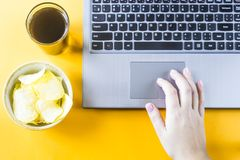 Snacking with junk food at the laptop. Chips and cola are near the laptop. A woman takes unhealthy junk food. Snack in the break between work Royalty Free Stock Photos