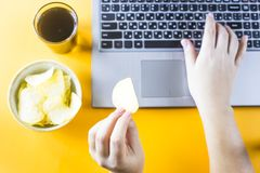 Snacking with junk food at the laptop. Chips and cola are near the laptop. A woman takes unhealthy junk food. Snack in the break between work Royalty Free Stock Image