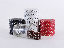 Chips and Dice. Red, black and white poker chips with two brown dice and a shot glass, on a white background Stock Image