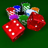 Chips and dices. Casino chips and transparent red dices on green table Royalty Free Stock Photo