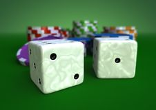 Chips and dices. Colorful chips on a green table with closeup of two white ivory dices Royalty Free Stock Photos