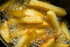 Chips, die im Schmieröl kochen. Stockfotografie