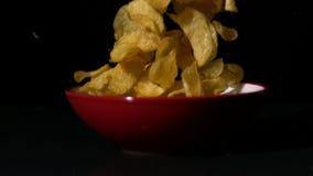 Chips, die in Schüssel auf schwarzer Oberfläche fallen stock video