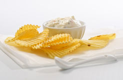 Chips and Dip. Rippled potato chips with a bowl of ranch style dip against a plain white background Stock Photos