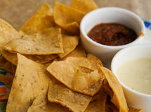 Chips and Dips. Tortilla chips on a colorful plate with two small bowls of dips on the side Stock Image