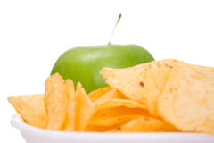 Chips on dish and apple. A white background. macro Stock Photo