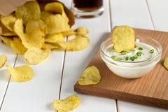 Chips in een document zak en een onderdompelende saus op een houten lijst Stock Fotografie