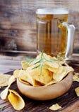 Chips in einer hölzernen Schüssel und in einem Bier Lizenzfreies Stockbild
