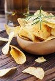 Chips in einer hölzernen Schüssel und in einem Bier Stockfoto