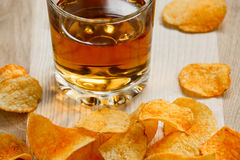 Chips en een glas appelsap op een houten lijst chips en een glas whisky royalty-vrije stock foto's