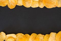 Chips food background ridged potato crisp frame. Chips food background. wavy ridged potato crisps mix. salty spicy crunchy slices frame on dark background stock photos