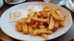 Chips and fried eggs Stock Photos