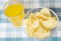 Chips and fruit juice. Bowl full of chips and fruit juice on the table royalty free stock photos