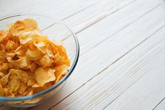 Chips in a glass cup on a white wooden backdrop, harmful food.  Stock Photos