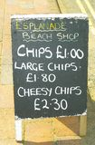 Chips, Large Chips and Cheesy Chips. A blackboard offering fast junk food at the UK seaside Royalty Free Stock Photography