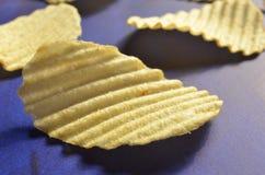 Chips met geribbeld of golven op blauwe oppervlakte stock foto