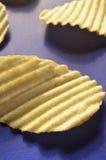 Chips met geribbeld of golven op blauwe oppervlakte stock afbeeldingen
